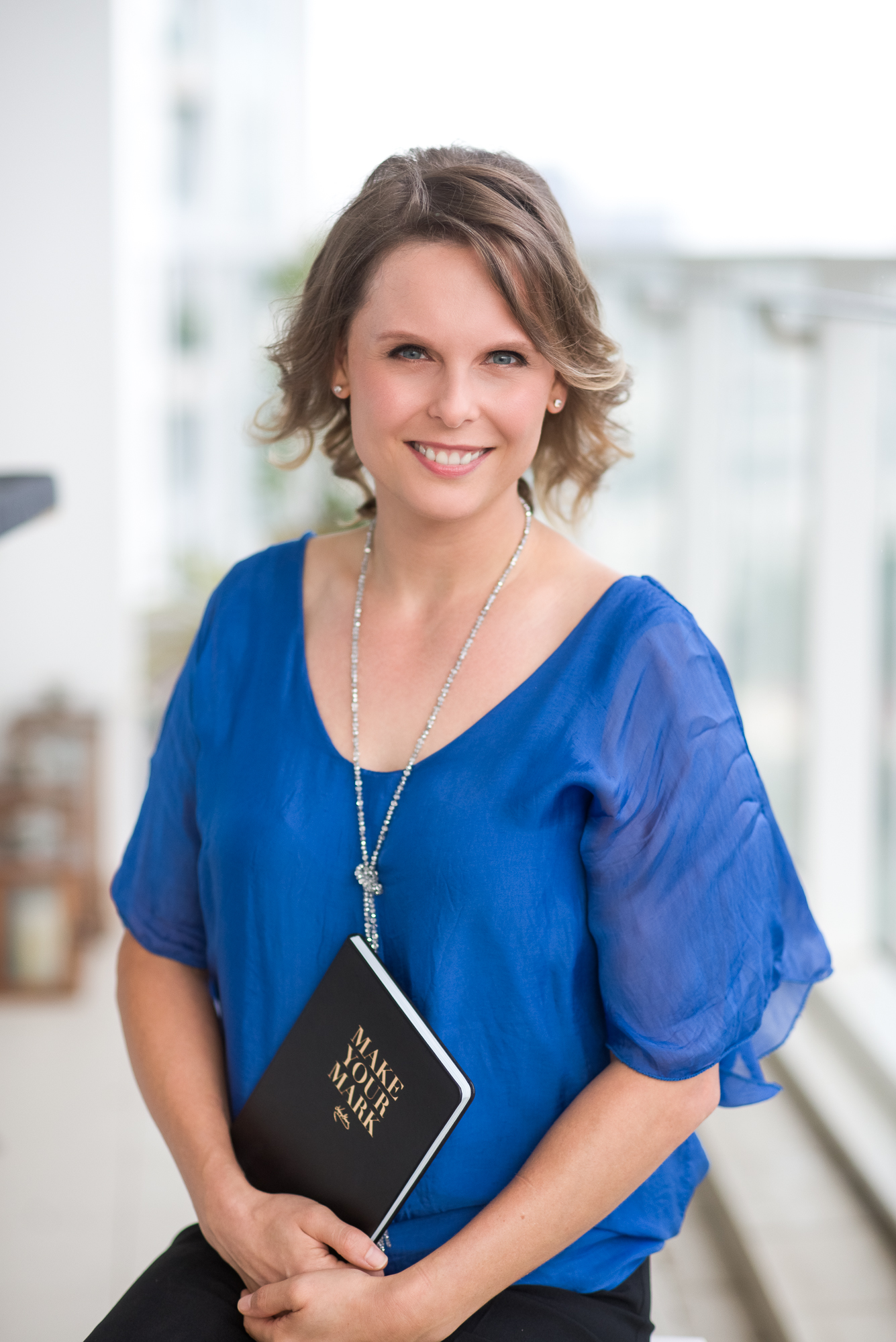 Sarah Cole wearing a blue top sitting with a book, posing for the camera