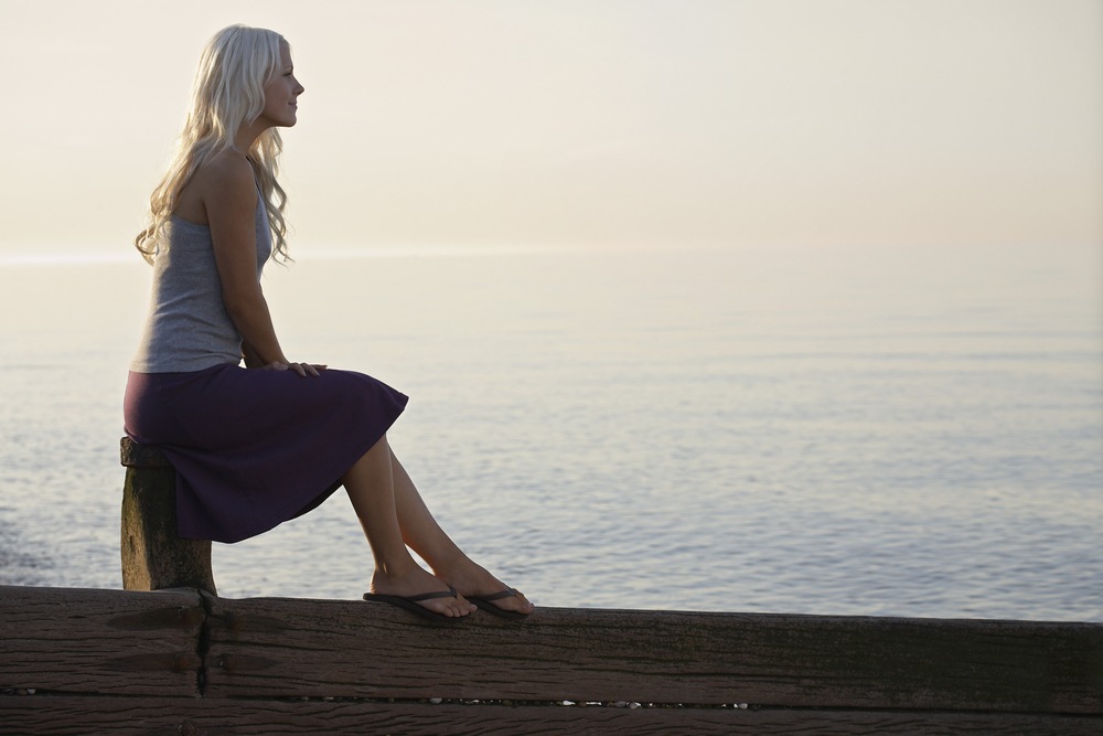 Young woman sitting on wooden bale on beach, side view